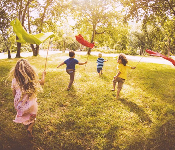 Friendly children playing in a park, running with colourful banners, in vintage style develop
